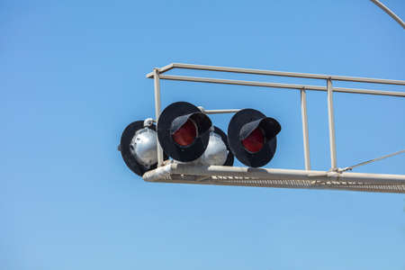 Railroad crossing light and barrier post with four lights and maintenance ramp