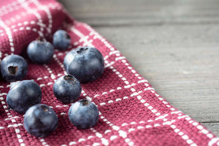 Grouping of blueberries on a folded dish towel on a rustic table