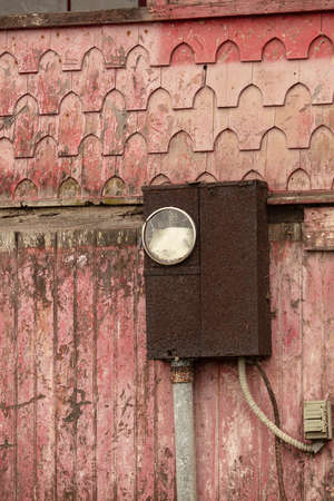 Old electrical box on a detereorating house with fading and peeling paint Stockfoto