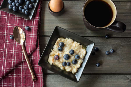 Breakfast bowl of oatmeal, honey, butter and blueberries with coffee and soft boiled eggs on a rustic table with a spoon and dish towel Imagens