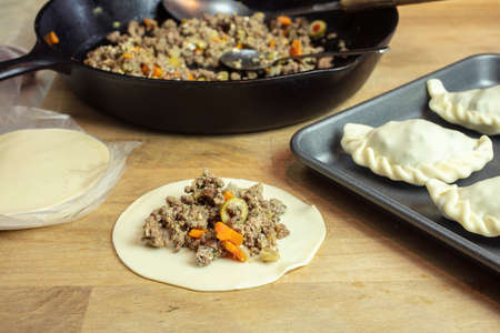 Preparation of Argentine empanadas with a ground beef, olives, carrots and spices stuffing placed on the dough and shaping them to bake on a sheet pan in the oven Imagens