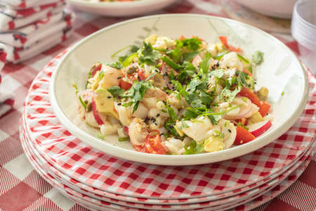 Ceviche plated in a bowl, surrounded by a variety of foods for a party celebration on a holiday
