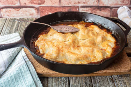 Apple pie baked in a cast iron skillet with a butter caramel sauce and golden crust