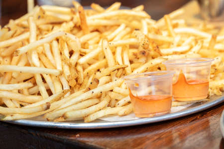 A large serving of string cut french fries with an aioli dip on the side Stock Photo