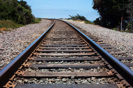 Railroad ties and track surrounded by shrubbery at a curve in Del Mar, California Imagens