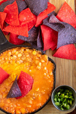 Mexican Chicken Chili made with corn and beans in a cast iron skillet, with red and blue tortilla chips and jalapeno peppers