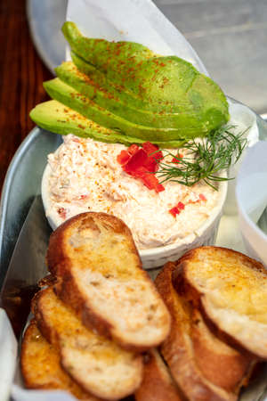 Serving of Salmon dip topped with avocado, dill and pepper, and a side of sliced buttered toast
