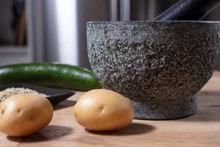 Mortar and pestle made of stone on a kitchen counter with potatoe, hemp seeds and cucumber Imagens