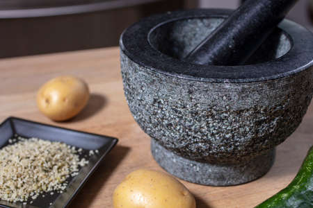 Mortar and pestle made of stone on a kitchen counter with potato, hemp seeds and cucumber