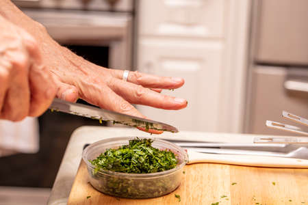 Hand of a chef chopping herbs as a demonstration in a food preparation class
