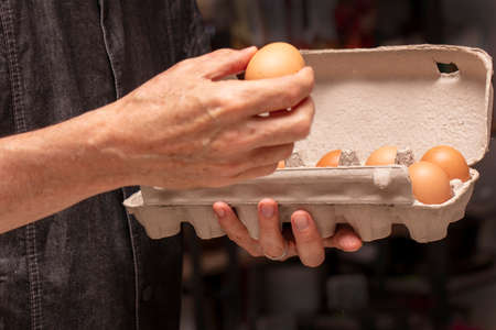 Chef holding an egg carton and a brown egg for meal preparation