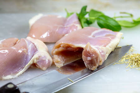 Skinless chicken thighs being preared for baking on a cutting board with basil and rosemary