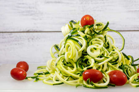 Spiralized Zucchini Noodles and Whole Miniature Tomatoes on a Cutting Board