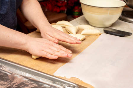 Hands on preparation of homemade bagels by kneading dough, cutting and shaping the dough