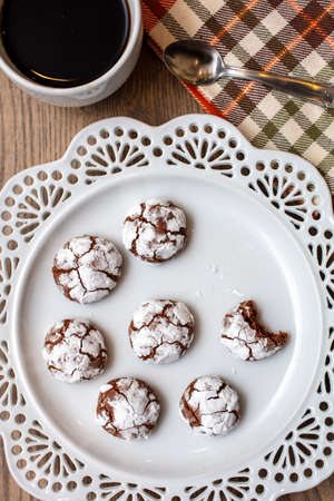 Table top setting with Chocolate Almond Crinkle cookies on a white plate with coffee for the holiday season