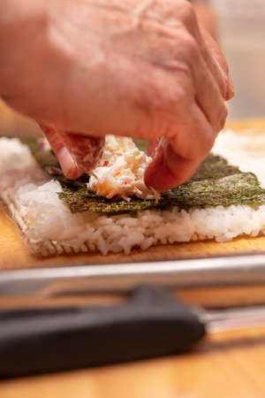 Sushi Roll demonstration on how to place ingredients for an outside Sushi Roll, with rice and seaweed