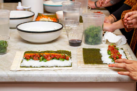 Students at a kitchen counter learning how to make Sushi Rolls in a class