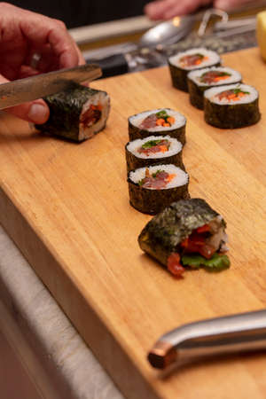 The process of making sushi and slicing during a chefs demonstration class in a home kitchen