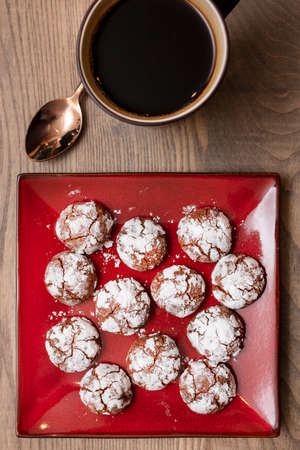 Coffee and Chocolate Almond Crinkle cookies with crackled powdered sugar on a red plate with a wood table background 스톡 콘텐츠