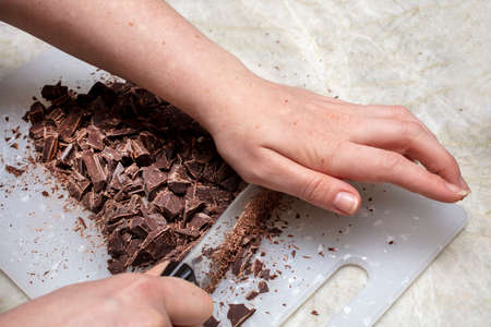 Chocolate beiing chopped into chunks for an ingredient in a baking item