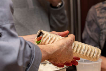 The process of making sushi during a chefs demonstration class in a home kitchen