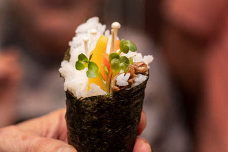 Chefs demonstration on how to make Shushi Cone rolls with rice, mushrooms, radish sprouts and mango 스톡 콘텐츠