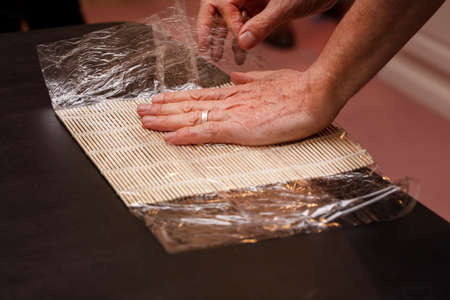 Chef preparing Sushi mat with plastic wrap to make a roll for a cooking class