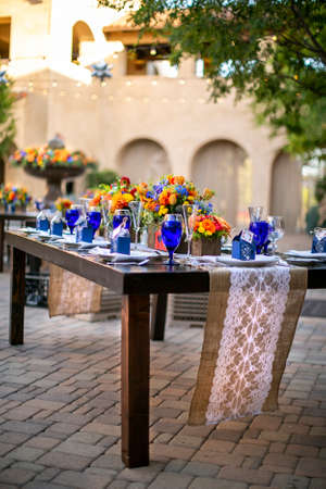 Table set for a patio wedding decorated with orange and yellow flower, blue and crystal wind glasses on a rustic table in a mission style patio garden