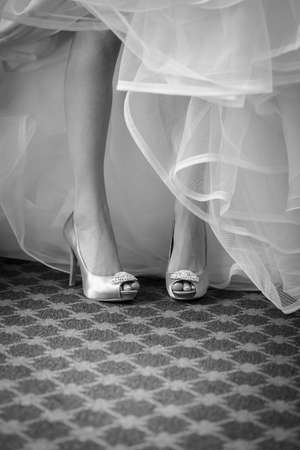 Black and white legs of bride in silk high healed pumps and tulle dress 免版税图像