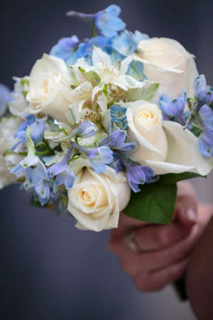 Bride holding a bouquet of wedding white roses and blue flowers
