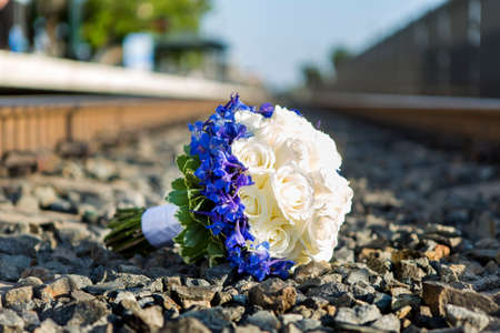 Bridal bouquet of white roses left on the gravel on a train track