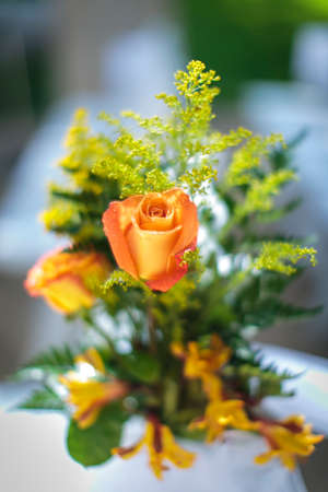 Yellow and pink rose with soft green filler in the background for a wedding decoratioin