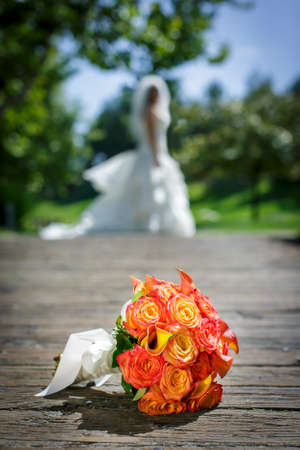 Wedding bouquet of yellow and prink roses tied with a white ribbon