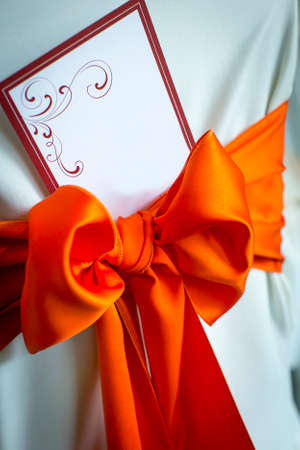 Wedding invitation card tied on whte fabric with red bow