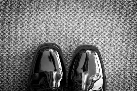 Black and whte textured and patterned carpet with pantent leather shoes seen from above