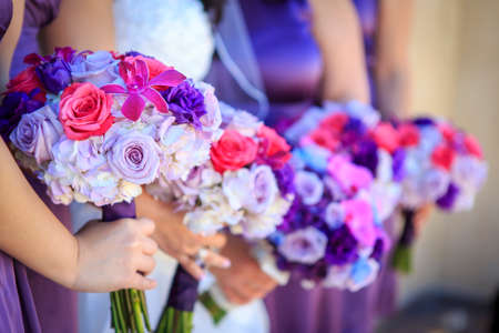 Lavendar, Pink and white roses and flower being held by bridesmaid standing in a line Imagens