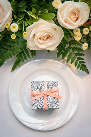 White roses and greenery above a white ceramic plate with a gift box  for a ceremony table setting