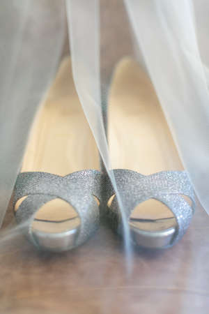 Toule wedding veil covering a pair of high-heeled bride shoes