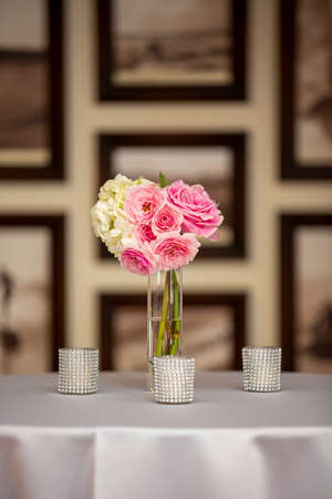 Bouquet of pink roses in a vase on a showcase table for preparation for a wedding