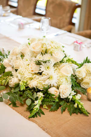 White roses and daisies decorating a table for a wedding party