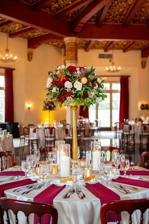 Wedding event dining setting with a color scheme of red and white with roses as a center piece Reklamní fotografie
