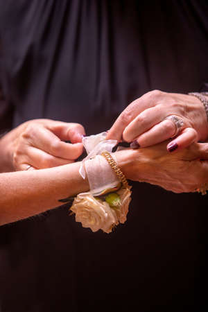 Bride to be having a tulle wrist band tied on her arm with a gold chain and roses, by her mother in preparation for her wedding ceremony