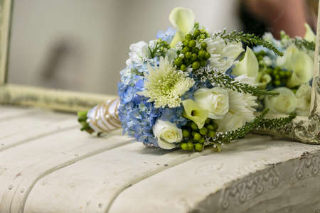 White vintage chest and mirror with a blue and white bridal bouquet on top