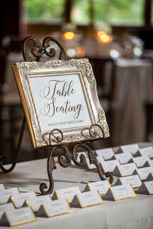 Gold trimmed folded name tagged cards for seating arrangments at a weeding ceremony