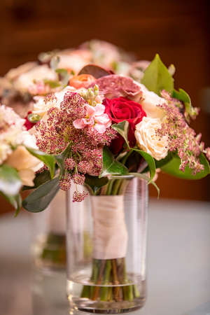Roses in red and white with filler flowers and greenery in a glass vase with water for a wedding ceremony