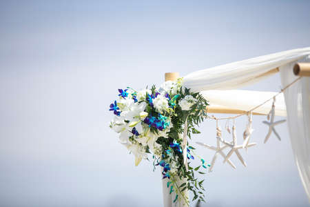 Outdoor wedding party gazebo decorated with blue and white flowers and starfish on a coastal sandy beach