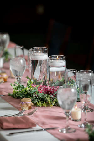 Pink themed wedding ceremony table setting with lit candles and crystal glasses Reklamní fotografie