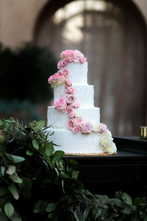 Wedding cake with white fondant and pink roses for an outdoor ceremony in spring