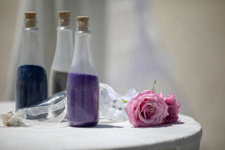 Three bottles filled with purple, blue and green sand on top of a table decorated with ribbon and piink roses for a wedding ceremony