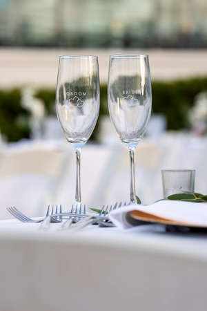 Crystal glasses for a bride and groom on a table set for a wedding ceremony